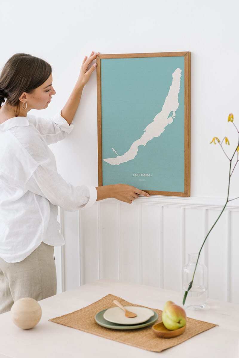 Woman decorating wall with lake topography art with Lake Baikal shape.